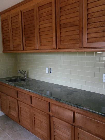 Laundry Room Cabinet With Louvered Doors. Stainless Steel Sink, Granite  Countertop And Tile Backsplash